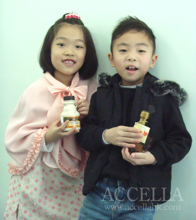 VivianL and EdgarW holding the bottles of maple syrup that they won for achieving the second-highest and highest, respectively, comprehension homework scores.
