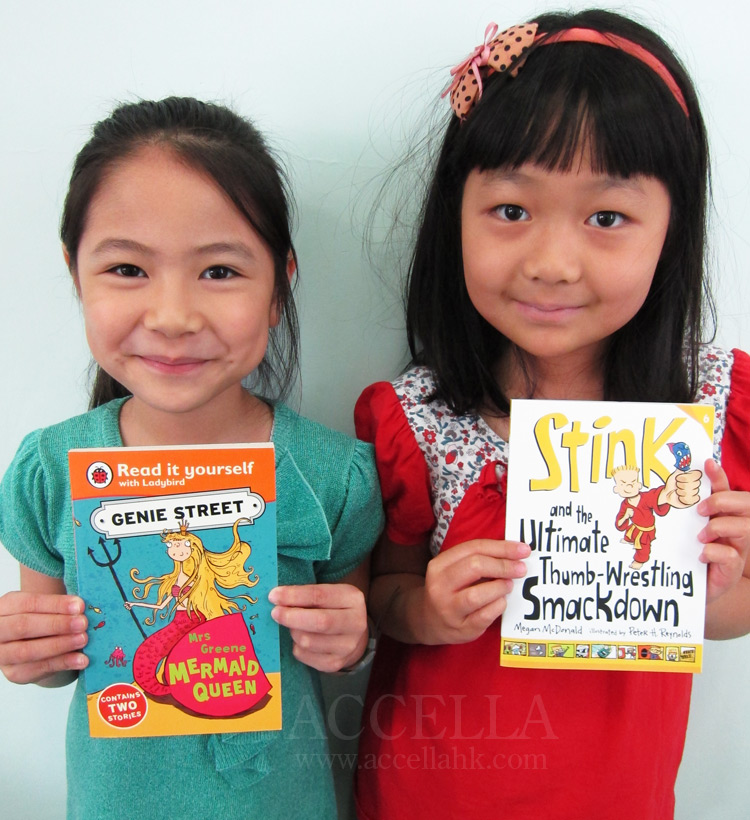 Katie and Mirella holding their latest book box selections.