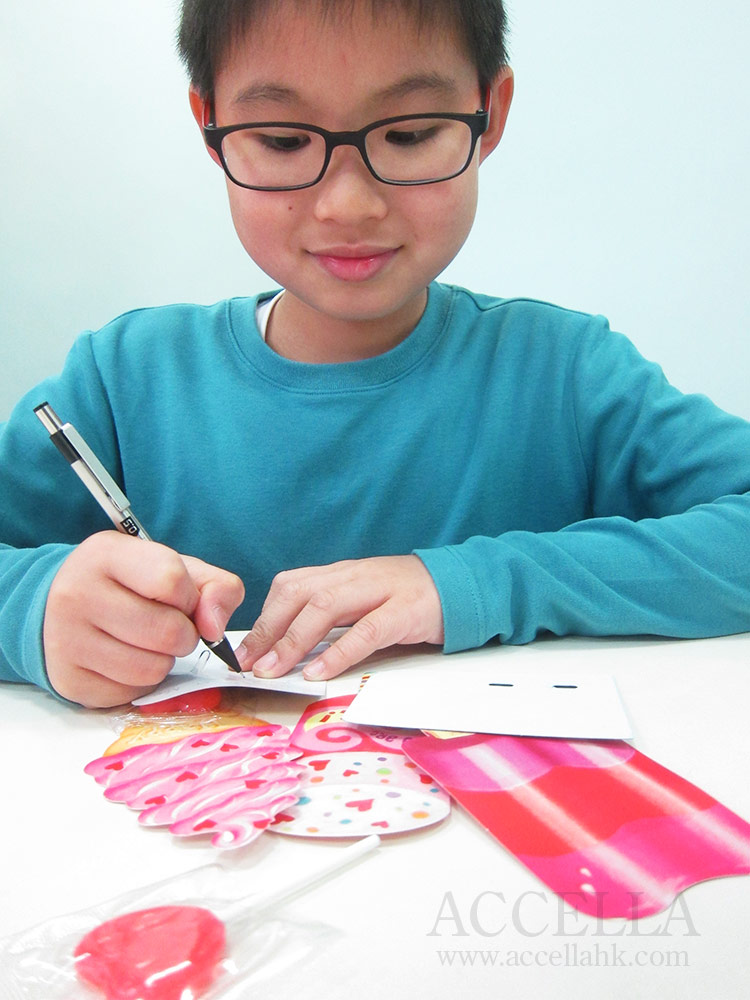 Ryan Y. making out his set of Valentine's Day cards in class.