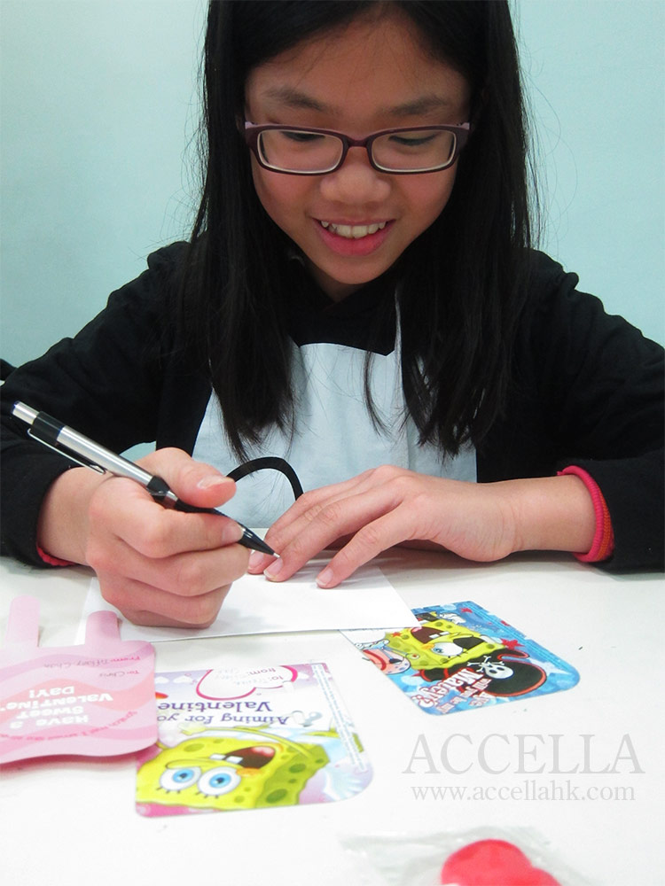 Tiffany C. writing Valentine's Day cards to her classmates.