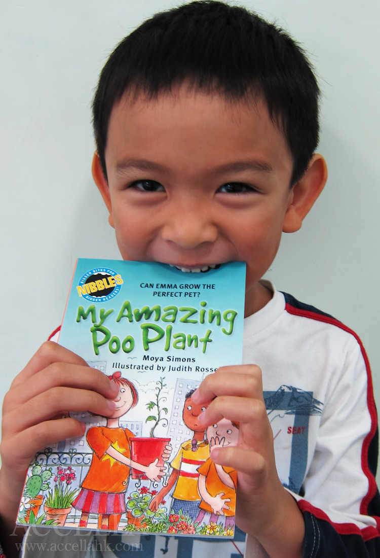 MarcusI pretending to take a bite out of his copy of 'My Amazing Poo Plant: Can Emma Grow the Perfect Pet?'.