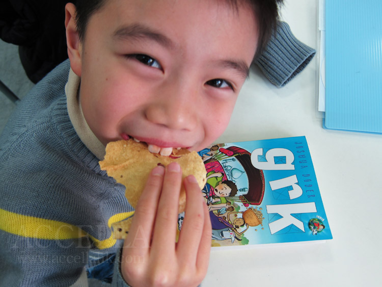 OliverH munching on a poppadom with his copy of Grk to his left.