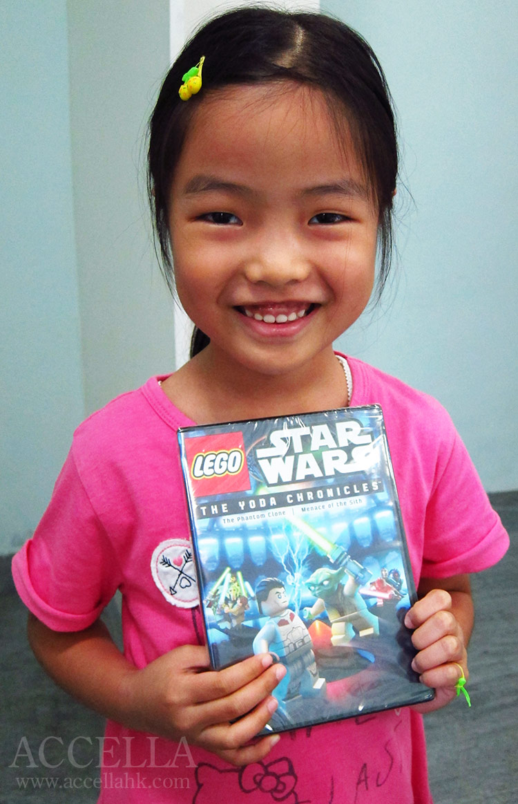 Alice C. holding the DVD that she earned through her own diligent effort.